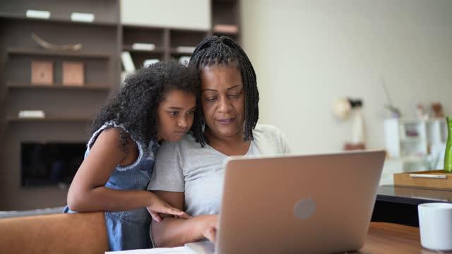 vídeos y material grabado en eventos de stock de mujer madura trabajando e hija (o nieta) llegando a casa - organizador personal