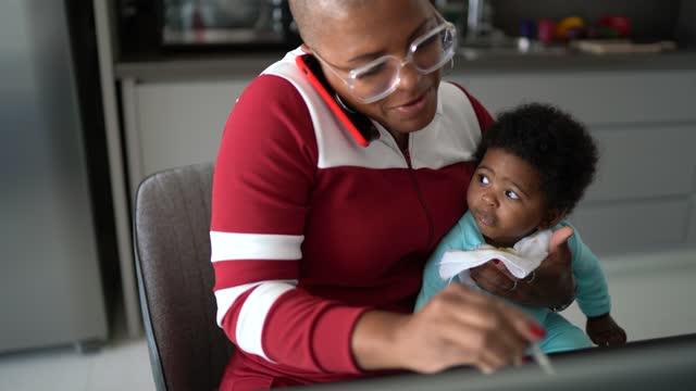 自宅で息子の世話をしながら、電話で働いて話している成熟した女性 - 髪の毛のない頭点の映像素材/bロール