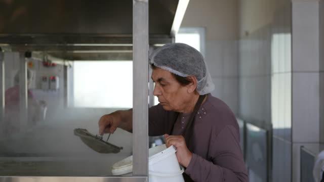 vidéos et rushes de femme mûr travaillant à une usine de production alimentaire - charlotte médicale ou sanitaire