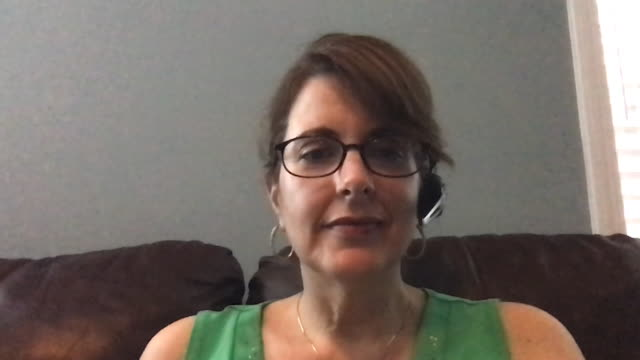 a mature woman working from home converses while on a video conference call. - adult stock videos & royalty-free footage