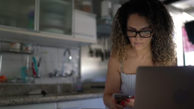 vídeos de stock, filmes e b-roll de mulher madura trabalhando em casa, usando laptop e smartphone - cozinha doméstica