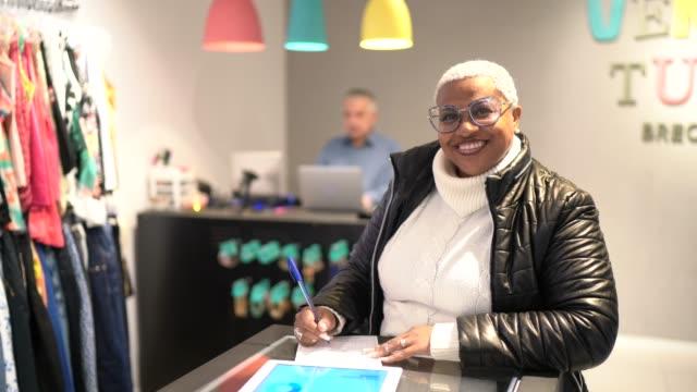 デジタルタブレットを使用して、店で働く成熟した女性 - 40 seconds or greater点の映像素材/bロール
