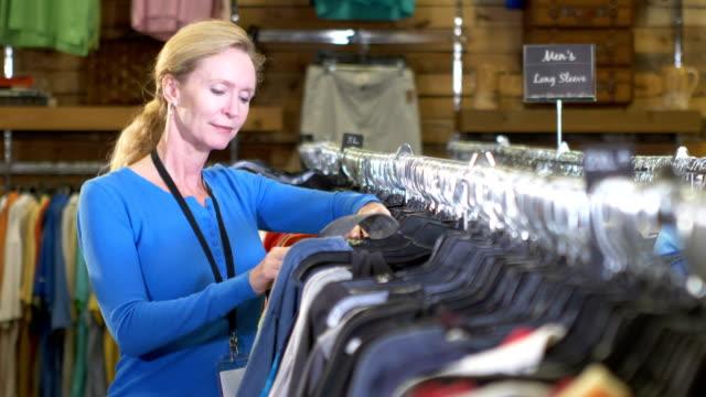stockvideo's en b-roll-footage met oudere vrouw werken in kleding winkel - kledingrek