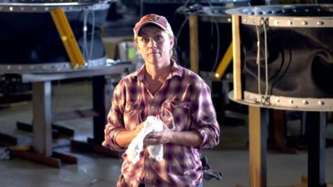 vidéos et rushes de femme d'âge mûr travaillant dans l'usine de fabrication de métal - endurance