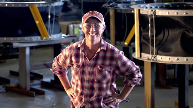 vídeos y material grabado en eventos de stock de mujer madura trabajando en la planta de fabricación de metal - gorra