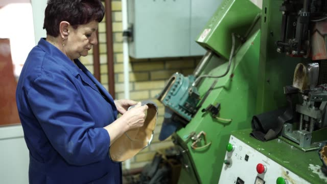 mature woman working in shoe factory on machine - service stock videos & royalty-free footage