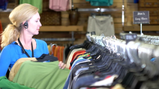 mature woman working in store, hanging clothes on rack - coathanger stock videos & royalty-free footage