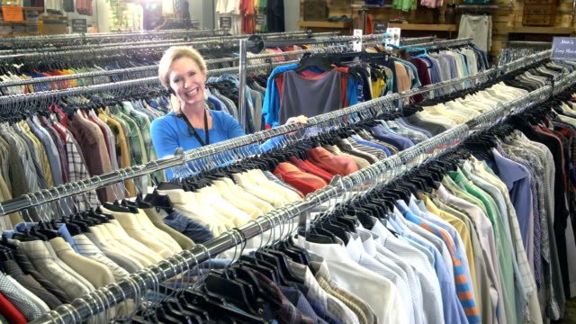 mature woman working in store, hanging clothes on rack - second hand stock videos & royalty-free footage