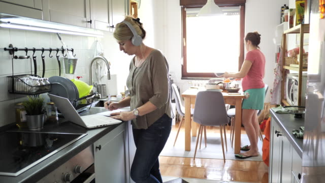 mature woman working on laptop in kitchen while family is setting up lunch table - messy stock videos & royalty-free footage