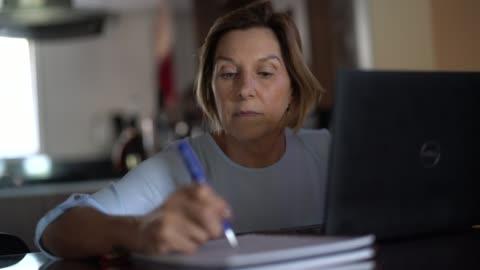 stockvideo's en b-roll-footage met oudere vrouw werken of studeren vanuit huis - study