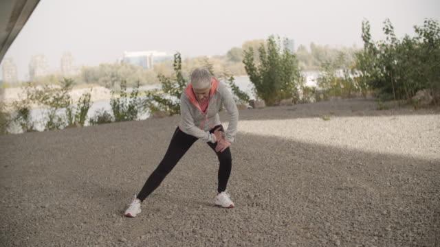 mogen kvinna som arbetar stretching övning. - kort hår bildbanksvideor och videomaterial från bakom kulisserna