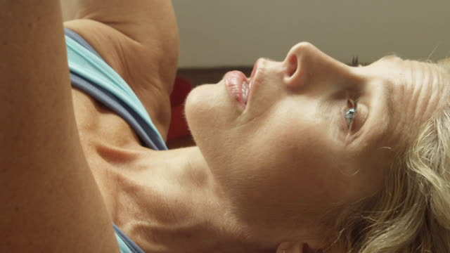 A mature woman works out in her home gym in slow motion.