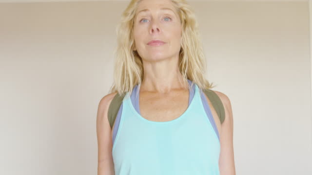 A mature woman works out in her home gym.