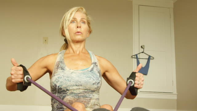 a mature woman works out in her home gym. - flexing muscles stock videos and b-roll footage