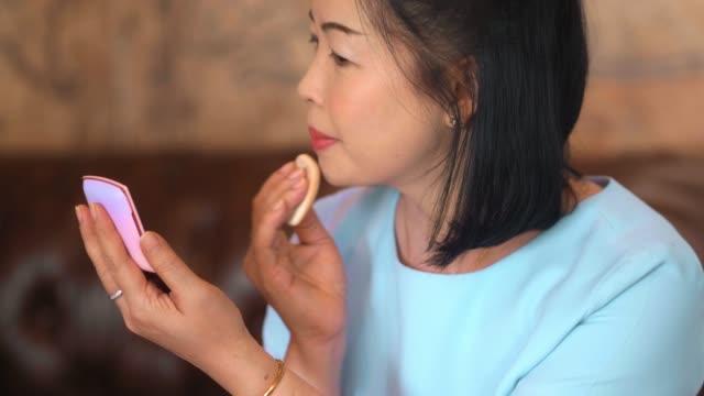 vídeos de stock, filmes e b-roll de as mulheres maduras aplicam um pó em uma face na frente do espelho - dermatologia