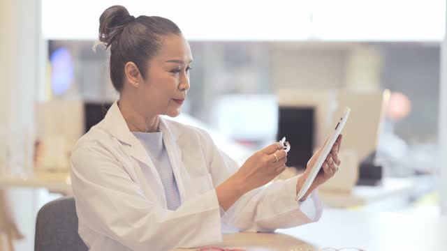 mature women doctor using digital tablet at his clinic - lens optical instrument stock videos & royalty-free footage