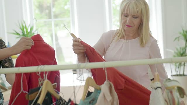 vídeos de stock e filmes b-roll de mature women enjoying shopping at modern fashion store - viciado em compras