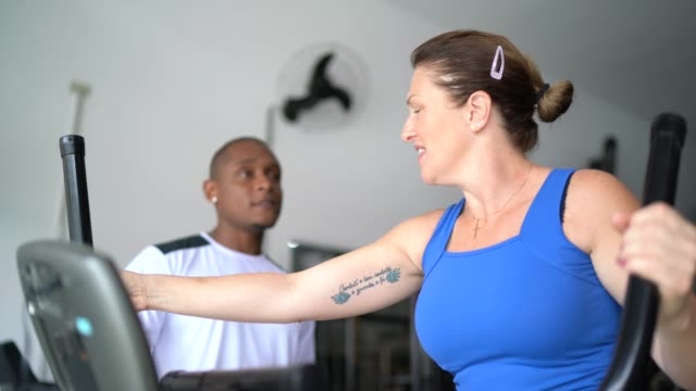 彼女の個人的なトレーナーの助けを借りてジムでカーディオステッパーで運動する成熟した女性 - 女子トラック競技点の映像素材/bロール