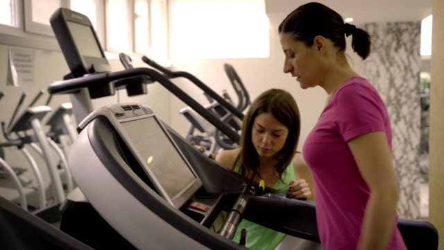 mature women have a cardio workout with personal trainer - durevolezza video stock e b–roll