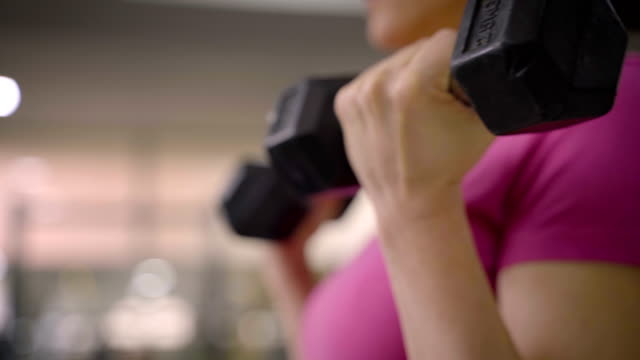 mature women have a dumbbell training with personal trainer.close up - bicep stock videos & royalty-free footage