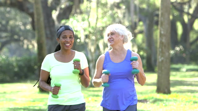 Mature women power walking in the park with hand weights