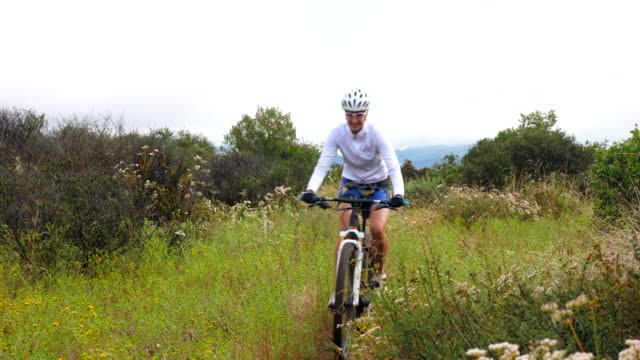 ms mature women riding across meadow during early morning mountain bike ride - bicycle trail outdoor sports stock videos & royalty-free footage