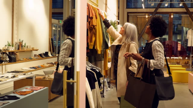 ms mature women shopping for for clothes together in boutique - geschäftliche aktivitäten stock-videos und b-roll-filmmaterial