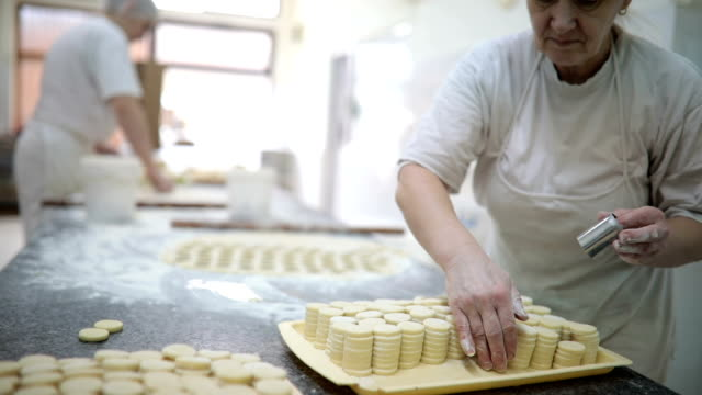 Mature women working at the bakery production