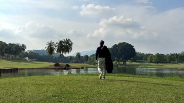 matured chinese man golfer carrying a golf bag looking away in the golf course - golf bag stock videos & royalty-free footage