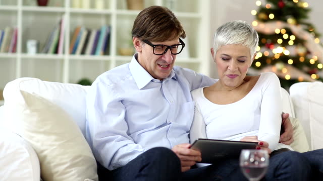 Mature-senior couple shopping over internet with credit card