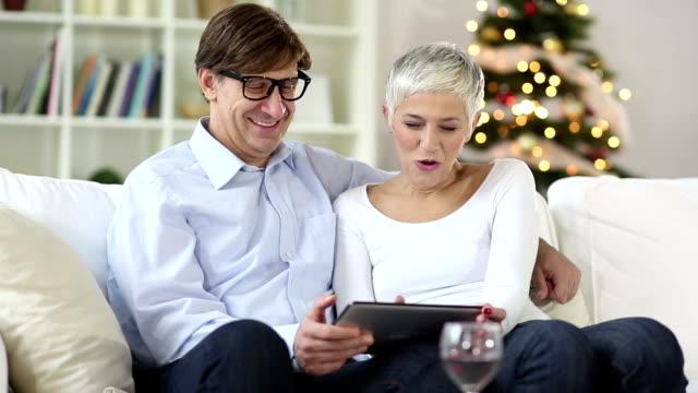 vidéos et rushes de mature couple senior au shopping sur internet avec une carte de crédit - cheveux gris
