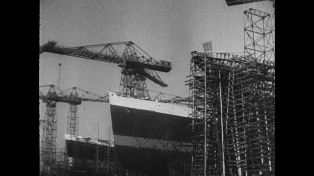 RMS Mauretania at dock men taking her apart with blow torches / man walking to work at the shipyard / men working on hulls of ships ships at sea