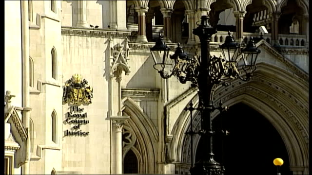 general views ENGLAND London Strand Royal Courts of Justice High Court / Max Clifford and another man walking along / Clifford poses for photographs...
