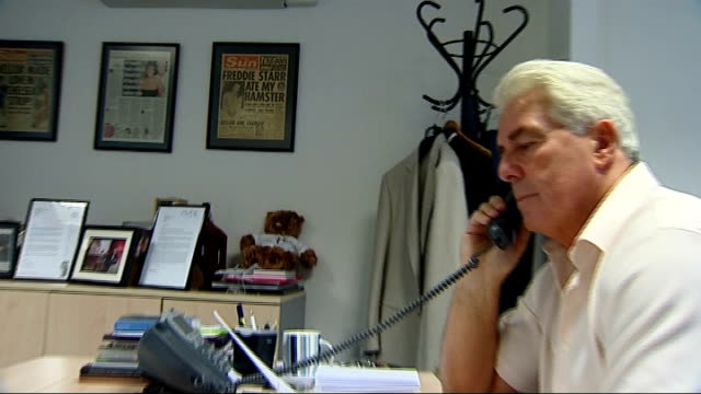 Max Clifford questioned by police on sexual assault allegations DATE Max Clifford at desk talking on phone ZOOM in to poster 'Freddie Starr ate my...