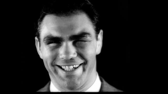Max Schmeling smiling and joking around with reporter after his win against Joe Louis / Schmeling's left eye is swollen