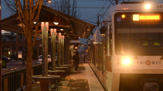Max train arrives at neighborhood station at dusk, Portland, Oregon