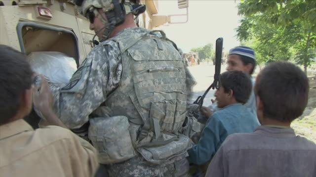 vídeos y material grabado en eventos de stock de may 1 2009 ms american soldier distributing beverages to local children / najil afghanistan - vehículo acorazado