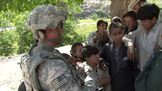 vídeos y material grabado en eventos de stock de may 1, 2009 american soldier talking to local children, all laughing / najil, afghanistan / audio - brazo humano