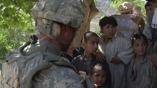 vidéos et rushes de may 1 2009 ms american soldier talking to local children / najil afghanistan / audio - uniforme militaire