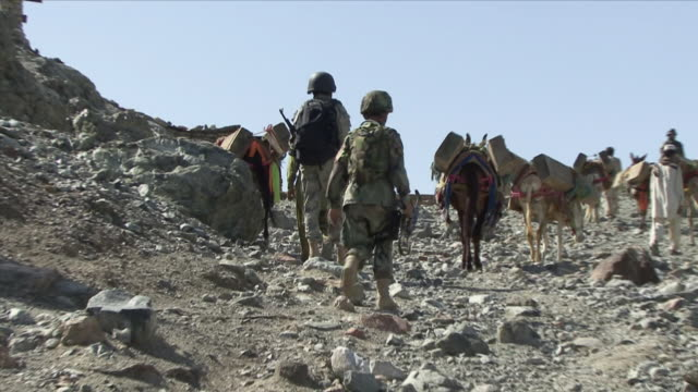 May 1 2009 MS ZO WS American soldiers and local people going up mountain with donkeys / Konar Valley Afghanistan
