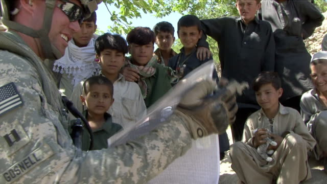 may 1, 2009 american soldiers asking questions to local children / najil, afghanistan / audio - brochure stock videos & royalty-free footage