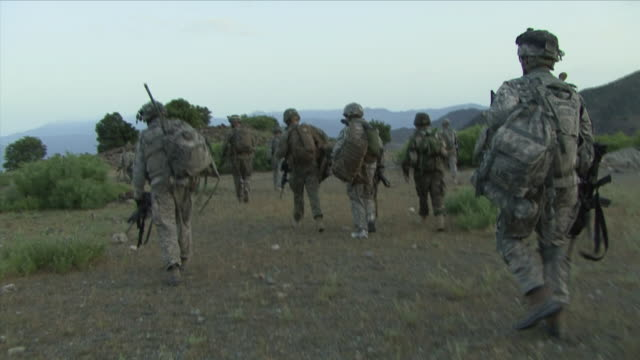 may 1 2009 ws pov american soldiers walking through field / konar valley afghanistan - kunar province stock videos & royalty-free footage