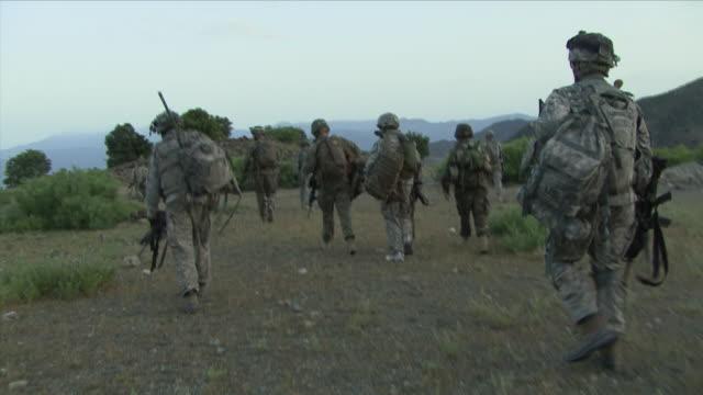 May 1 2009 WS POV American soldiers walking through field / Konar Valley Afghanistan