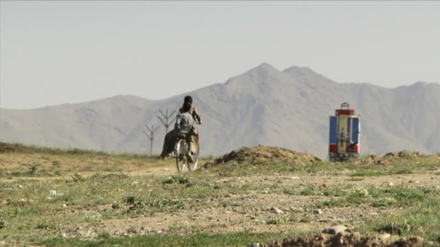 may 1, 2009 boys sharing bike / bagram, afghanistan - bagram stock videos & royalty-free footage