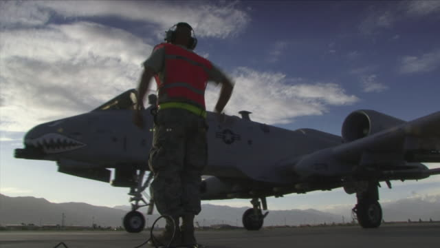 may 1, 2009 fairchild a10 fighter plane taking off, guided by ground crew member / bagram, afghanistan - bagram stock videos & royalty-free footage