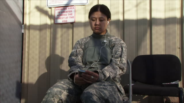 May 1 2009 MS Female American soldier listening to music from mp3 player / Bagram Afghanistan