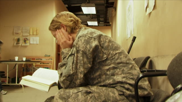 May 1 2009 MS Female American soldier reading book in waiting room / Bagram Afghanistan