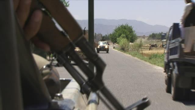May 1 2009 CU Hand holding gun in convoy car / Konar Valley Afghanistan
