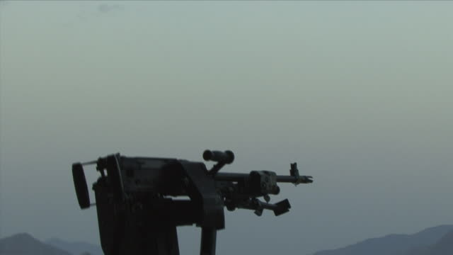 May 1 2009 WS Helicopter taking off American soldier sitting down by gun / Konar Valley Afghanistan