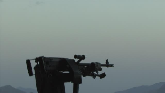 may 1 2009 ws helicopter taking off american soldier sitting down by gun / konar valley afghanistan - heckklappe teil eines fahrzeugs stock-videos und b-roll-filmmaterial
